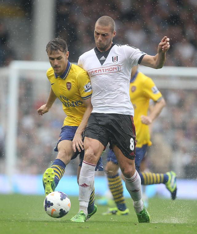 Arsenal's Aron Ramsey gets tackled by Fulham Pajtim Kasami during the Barclays Premier League match at Craven Cottage, London.