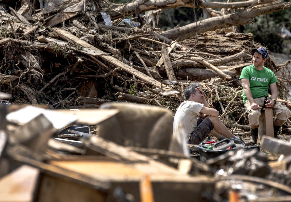 Residents are seen between debris in Marienthal, western Germany, Sunday, July 18, 2021. Heavy rains caused mudslides and flooding in the western part of Germany. Multiple have died and are missing as severe flooding in Germany turned streams and streets into raging, debris-filled torrents that swept away cars and toppled houses. (Boris Roessler/dpa via AP)