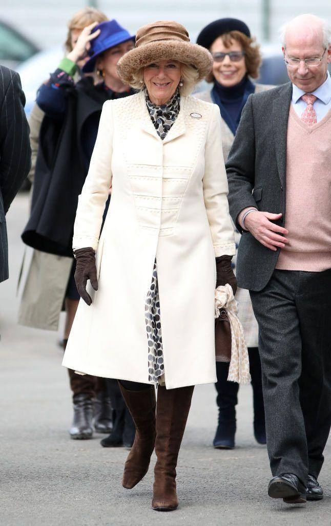 <p>The Duchess of Cornwall attended 'Ladies Day' at the Cheltenham Races wearing a structured white coat with intricate embellishments over a polka dot dress. She topped off the look with chocolate brown boots, gloves, and bag, a tan fur-trimmed hat, and pearl drop earrings. </p>