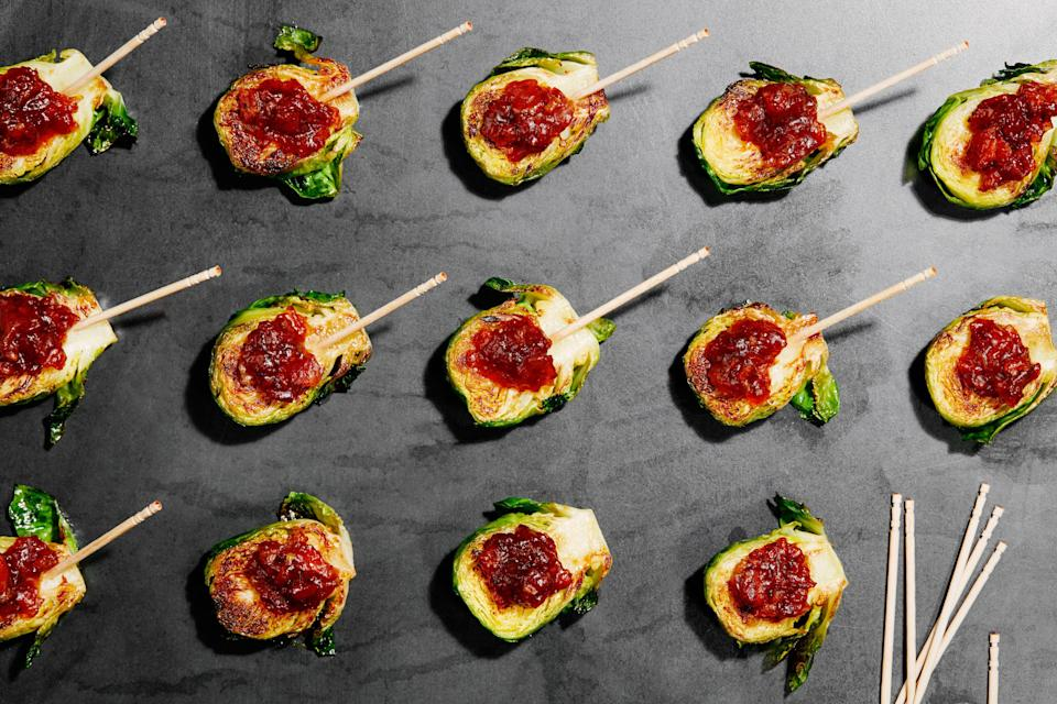 """Lollipop sticks not required for these cute little hors d'oeuvres of brussels sprouts topped with a bacon and dried apricot jam. <a href=""""https://www.epicurious.com/recipes/food/views/brussels-sprouts-with-bacon-jam?mbid=synd_yahoo_rss"""" rel=""""nofollow noopener"""" target=""""_blank"""" data-ylk=""""slk:See recipe."""" class=""""link rapid-noclick-resp"""">See recipe.</a>"""