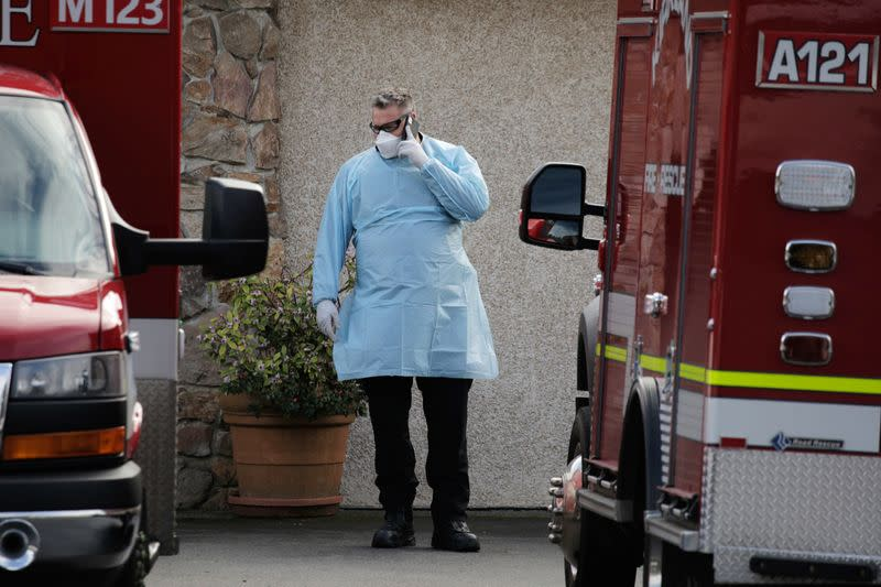 A medic talks on the phone while others transport a patient to an ambulance at the Life Care Center of Kirkland, the long-term care facility linked to several confirmed coronavirus cases in the state, in Kirkland