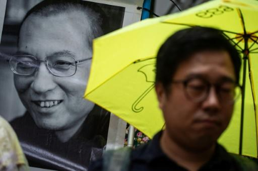 A protester stands in front of a portrait of Liu Xiaobo during a march to the Chinese liaison office in Hong Kong