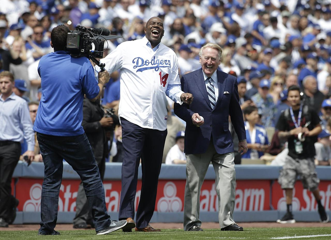 Los Angeles Dodgers part-owner Magic Johnson, center left, and broadcaster Vin Scully laugh as they walk on the field before a baseball game against the San Francisco Giants, Friday, April 4, 2014, in Los Angeles. (AP Photo/Jae C. Hong)