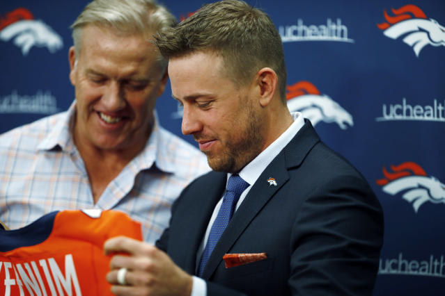Case Keenum, front, admires his new jersey as John Elway, general manager of the Denver Broncos, looks on during a news conference to introduce him as the new starting quarterback of the Broncos at the NFL football team's headquarters Friday, March 16, 2018, in Englewood, Colo. (AP Photo/David Zalubowski)