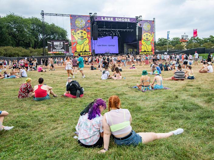 Festival goers sit on grass in front of Lake Shore stage at Lollapalooza Music Festival.