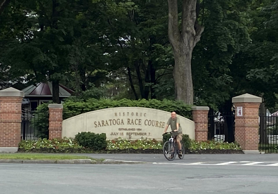 A bicyclist rides past the locked gates at the Saratoga Race Course in Saratoga Springs, N.Y., Thursday, July 16, 2020. A Saratoga season like no other is underway, with fans barred from attending the start of the 152nd meet in track history and most likely the entire 40 days of racing. (AP Photo/John Kekis)