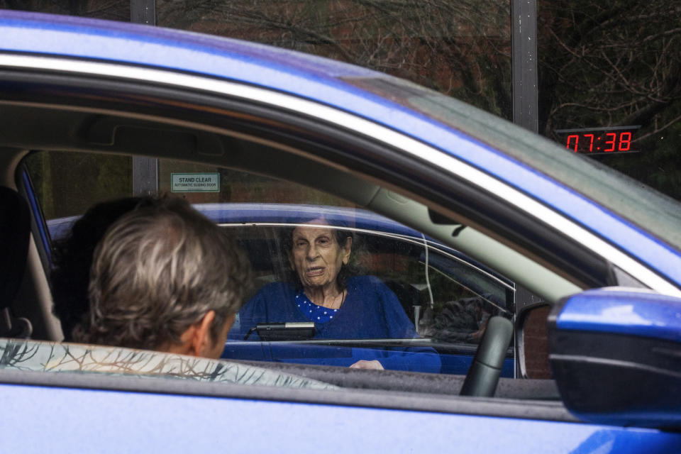 Nursing home resident Jeannette Levy, 95, speaks with family members during a drive-by visit at the Hebrew Home at Riverdale in the Bronx during Thanksgiving Day, Thursday, Nov 26, 2020, in New York. (AP Photo/Eduardo Munoz Alvarez)