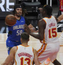 Orlando Magic guard Cole Anthony (50) looks for an opening past Atlanta Hawks guard Bogdan Bogdanovic (13) and center Clint Capela (15) in the first half of an NBA basketball game Thursday, May 13, 2021 in Atlanta. (AP Photo/Tami Chappel)