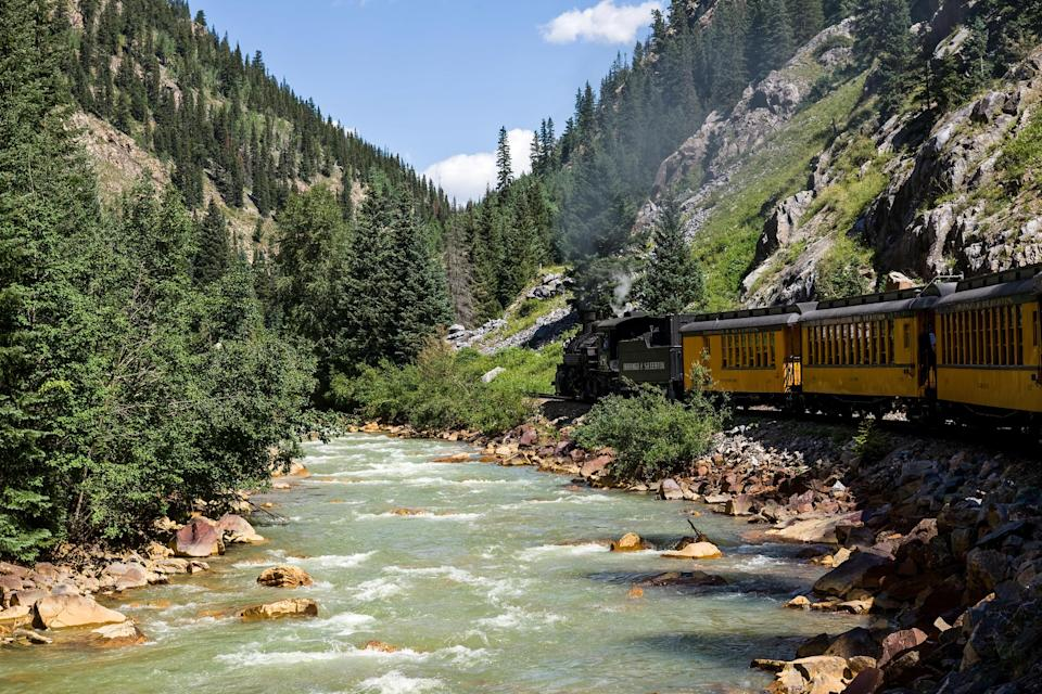A train passes by a river in the mountains