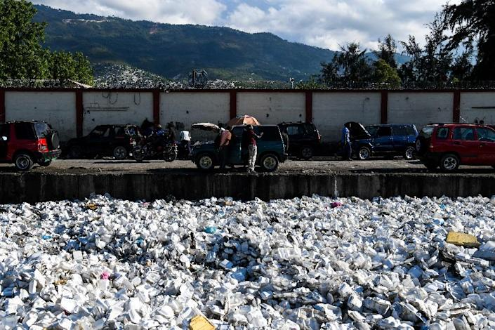 Plastic waste is seen floating on a sewage canal in the Haitian capital Port-au-Prince, on April 23, 2019. Around 180 governments Have agreed on a new UN accord to regulate the export of plastic waste (AFP Photo/CHANDAN KHANNA)