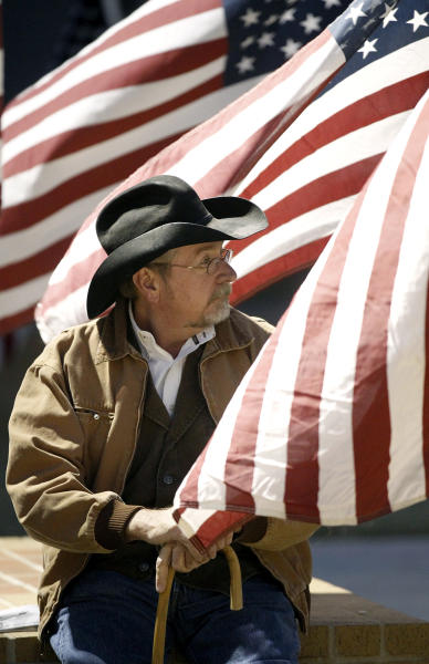 A candlelight vigil participant rests prior to the start of a memorial service held Saturday, Nov. 17, 2012 in Centennial Plaza in Midland, Texas in honor of four veterans who were killed when a freight train hit a parade float Thursday. (AP Photo/Midland Reporter-Telegram, James Durbin)