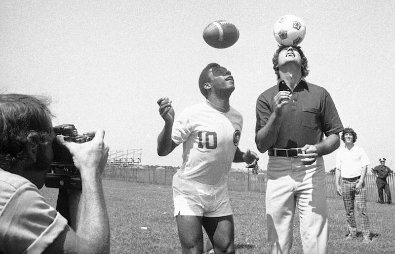 """FILE - In this Aug. 5, 1975, file photo, New York Jets quarterback Joe Namath, right, bounces soccer ball on his head while Pele, of the New York Cosmos, uses his head to get a feel for the pigskin at the Jets' training camp at Hofstra University in Hempstead, N.Y. Pele, who has had an interest in the NFL since his Cosmos days in the 1970s, will appear in a commercial during Sunday night's game for Subway as their latest """"Famous Fan'' and first global brand ambassador. Pele said, """"I still remember once, Joe Namath asked me if I have ever thought of kicking field goals in the NFL. My answer to him is that I cannot score any goals with a helmet on."""" (AP Photo/Ray Howard, File)"""