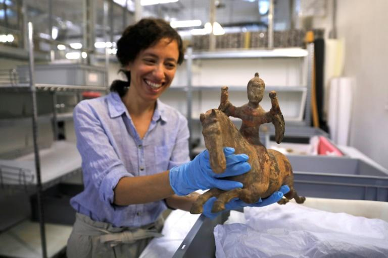 Curator Morag Wilhelm holds an artefact which belonged to Sigmund Freud at the Israel Museum in Jerusalem on July 12, 2018