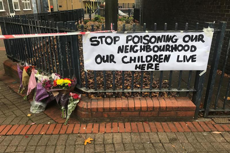 Floral tributes and a sign near where Ian Tomlin was killed: PA