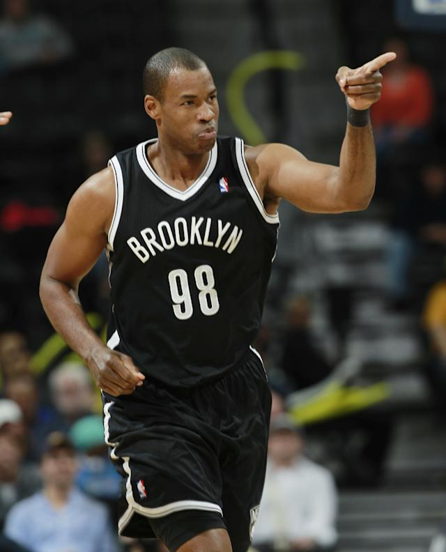 Brooklyn Nets center Jason Collins acknowledges the cheers from his teammates after Collins hit a basket against the Denver Nuggets late in the fourth quarter of the Nets' 112-89 victory in an NBA basketball game in Denver on Thursday, Feb. 27, 2014. (AP Photo/David Zalubowski)