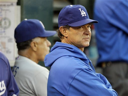 Los Angeles Dodgers manager Don Mattingly, right, looks to the bullpen in the fourth inning of their baseball game against the Oakland Athletics in Oakland, Calif., Tuesday, June 19, 2012. At left is first base coach Davey Lopes. (AP Photo/Eric Risberg)