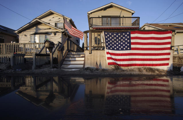 U.S. flags are displayed on flood-damaged homes in the Breezy Point section of Queens, N.Y., Nov. 28, 2012. (Photo: Mark Lennihan/AP)