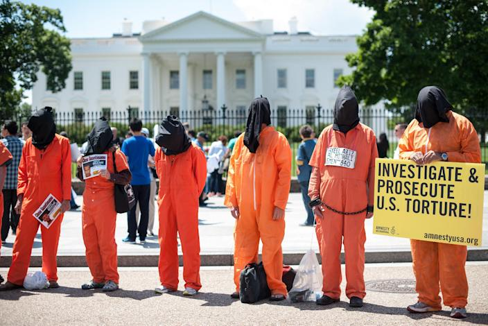Protestors wearing orange prisoner jumpsuits call for the closure of the Guantanamo Bay detention facility in front of the White House in Washington on May 23, 2014 (AFP Photo/Nicholas Kamm)