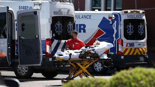 PHOTO: A person is brought to a medical transport vehicle from Banner Desert Medical Center as several transports and ambulances are shown parked outside the emergency room entrance, June 16, 2020, in Mesa, Ariz. (Ross D. Franklin/AP)