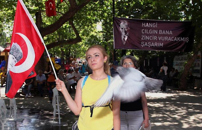 Turks, some of them holding national flags with images of Turkey's founder Kemal Ataturk, stand in a silent protest in Kugulu Park in Ankara, Turkey, Wednesday, June 19, 2013. After weeks of sometimes-violent confrontation with police, Turkish protesters have found a new form of resistance: standing still and silent. (AP Photo/Burhan Ozbilici)