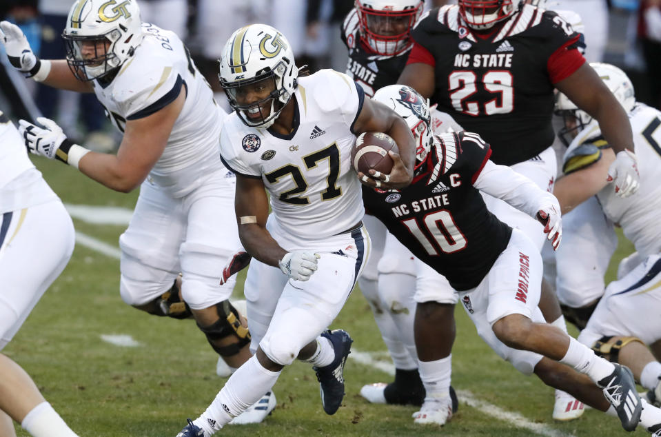 Georgia Tech running back Jordan Mason (27) runs through the North Carolina State defense during the first half of an NCAA college football game in Raleigh, N.C., Saturday, Dec. 5, 2020. (Ethan Hyman/The News & Observer via AP, Pool)
