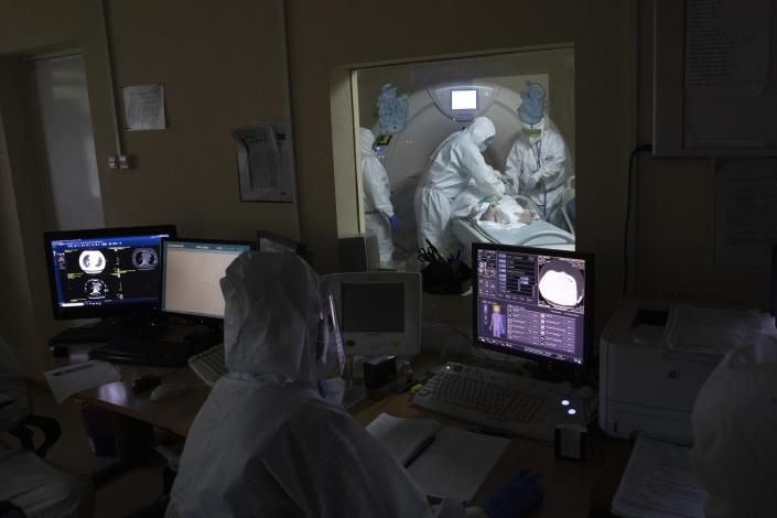 In this photo taken on Friday, May 15, 2020, Dr. Osman Osmanov, center, and Dr. Vitaly Mushkin, right, prepare a coronavirus patient on artificial lung respiration for computer tomography screening at an intensive care unit of the Filatov City Clinical Hospital in Moscow, Russia. Moscow accounts for about half of all of Russia's coronavirus cases, a deluge that strains the city's hospitals and has forced Osmanov to to work every day for the past two months, sometimes for 24 hours in a row. (AP Photo/Pavel Golovkin)