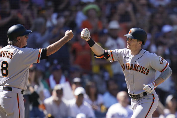 San Francisco Giants' Mike Yastrzemski, right, is greeted by third base coach Ron Wotus after hitting a two-run home run during the second inning of a baseball game against the San Diego Padres, Thursday, Sept. 23, 2021, in San Diego. (AP Photo/Gregory Bull)