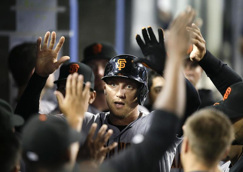 San Francisco Giants' Hunter Pence, center, is greeted by teammates after hitting a solo home run during the second inning of a baseball game against the Los Angeles Dodgers on Thursday, Sept. 12, 2013, in Los Angeles. (AP Photo/Jae C. Hong)