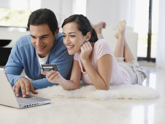 Barefoot couple lying on floor at home shopping on a laptop with credit card.