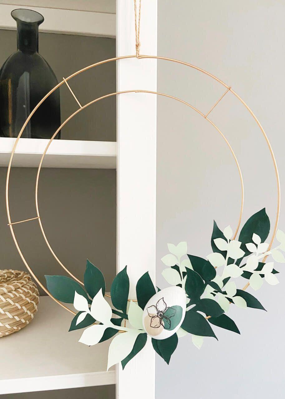 """<p>Perhaps you're on the hunt for an Easter wreath that looks a wee bit more modern for this year's decorations. In that case, you can make this sleek Easter wreath using plastic eggs, painted leaves, and a wire wreath form.</p><p><strong>Get the tutorial at <a href=""""https://www.isoscella.co.uk/blog/diy-paper-easter-wreath"""" rel=""""nofollow noopener"""" target=""""_blank"""" data-ylk=""""slk:Isoscella"""" class=""""link rapid-noclick-resp"""">Isoscella</a>.</strong></p><p><a class=""""link rapid-noclick-resp"""" href=""""https://go.redirectingat.com?id=74968X1596630&url=https%3A%2F%2Fwww.walmart.com%2Fip%2FApple-Barrel-20529EX-Matte-Acrylic-Craft-Paint-Christmas-Green-2-fl-oz%2F157045737&sref=https%3A%2F%2Fwww.thepioneerwoman.com%2Fhome-lifestyle%2Fcrafts-diy%2Fg35698457%2Fdiy-easter-wreath-ideas%2F"""" rel=""""nofollow noopener"""" target=""""_blank"""" data-ylk=""""slk:SHOP ACRYLIC PAINT"""">SHOP ACRYLIC PAINT</a></p>"""