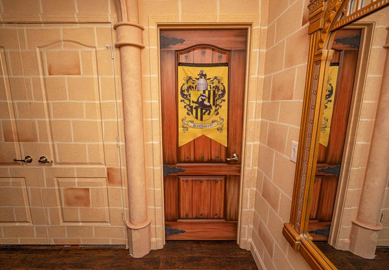 PIC BY @LOMA HOMES / CATERS NEWS AGENCY (PICTURED- Another door with the hufflepuff shield ) - Harry Potter fans looking for a first post-lockdown trip can put this place at the top of their list - a night in a Hogwarts- themed Airbnb. The eight-bedroom home, called ' Wizard's Way' is based in Florida, US, near the Universal Orlando Resort. There are rooms based on the four houses Gryffindor, Hufflepuff, Ravenclaw, and Slytherin and each bathroom has its own Harry Potter theme, from Hedwig and the Ministry of Magic to Dobby, and Sirius Black. One of the bedrooms features an interactive car-shaped bed which is inspired by the scene where Harry and Ron get stuck in the Willow Tree of the second part of the film series. - SEE CATERS COPY