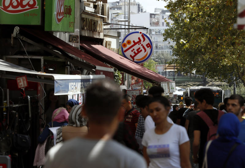In this photo taken on Tuesday, Aug. 20, 2019, people walk past Syrian restaurants in the Istanbul neighborhood of Aksaray, where many Syrians live. Syrians say Turkey has been detaining and forcing some Syrian refugees to return back to their country the past month. The expulsions reflect increasing anti-refugee sentiment in Turkey, which opened its doors to millions of Syrians fleeing their country's civil war. (AP Photo/Lefteris Pitarakis)