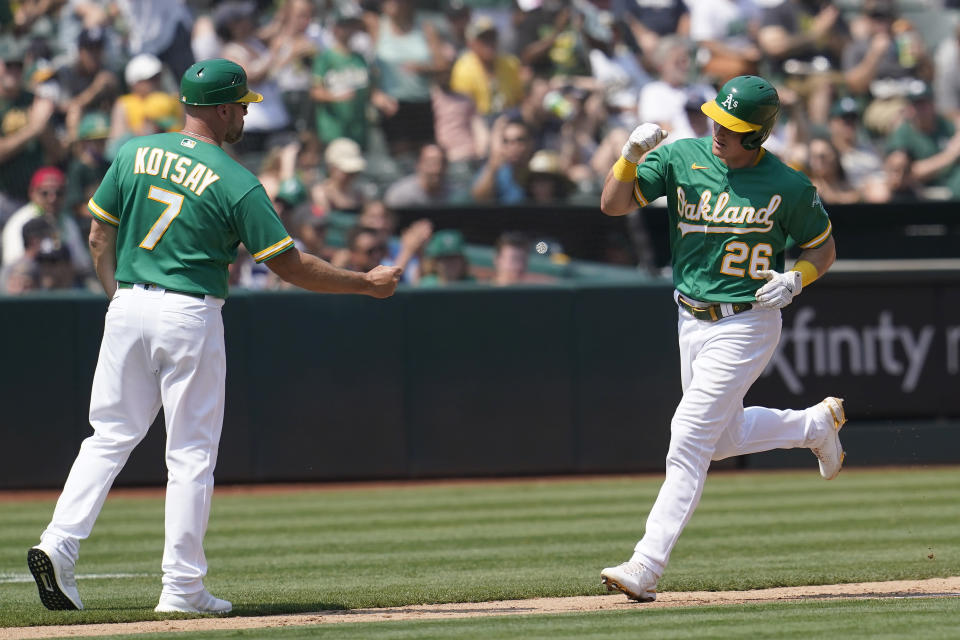 Oakland Athletics' Matt Chapman, right, is congratulated by third base coach Mark Kotsay after hitting a home run against the New York Yankees during the fourth inning of a baseball game in Oakland, Calif., Saturday, Aug. 28, 2021. (AP Photo/Jeff Chiu)