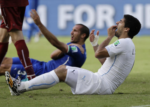 Uruguay's Luis Suarez holds his teeth after running into Italy's Giorgio Chiellini's shoulder during the group D World Cup soccer match between Italy and Uruguay at the Arena das Dunas in Natal, Brazil, Tuesday, June 24, 2014. (AP Photo/Ricardo Mazalan)