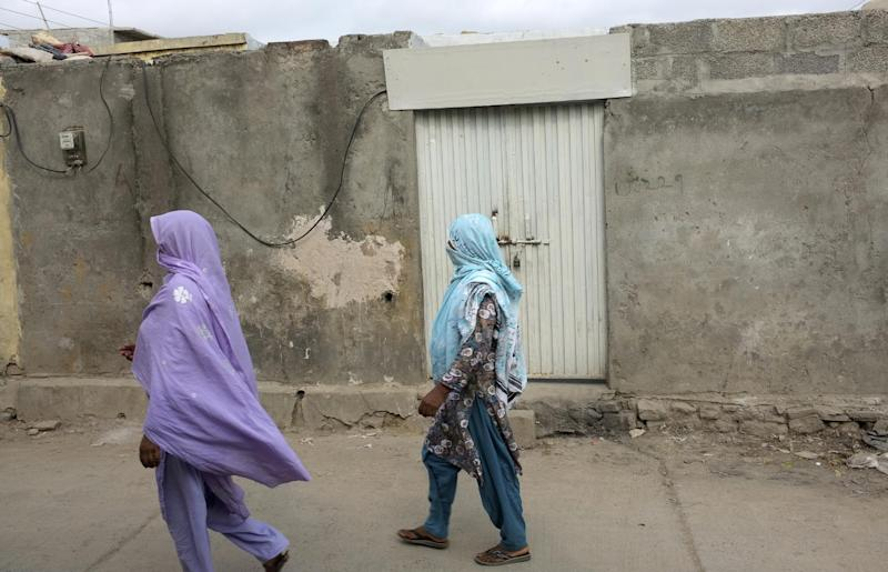 Local women walk past the locked house of a Christian girl in a suburb of Islamabad, Pakistan on Monday, Aug. 20, 2012. Pakistani authorities arrested a Christian girl and are investigating whether she violated the country's strict blasphemy laws after furious neighbors surrounded her house and demanded police take action, a police officer said Monday. The arrest of the girl and outrage among the local community demonstrates the deep emotion that suspected blasphemy cases can evoke in this conservative Muslim country, where rising extremism often means religious minorities live in fear of persecution.(AP Photo/B.K. Bangash)