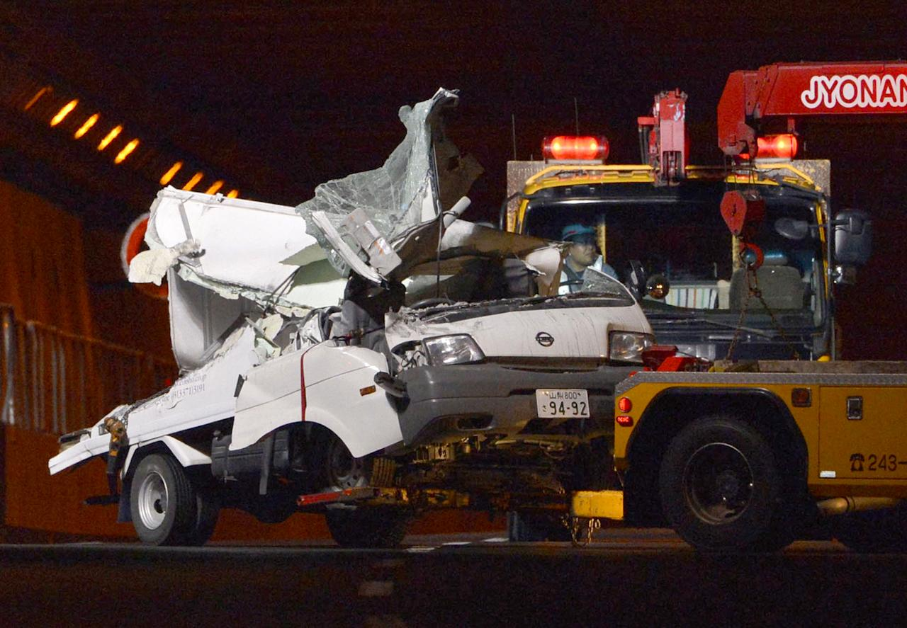 A tow truck hauls the wreckage of a truck, which was crushed in Sunday's accident, out of the Sasago Tunnel on the Chuo Expressway in Koshu, Yamanashi Prefecture, central Japan, early Monday, Dec. 3, 2012. Concrete ceiling panels fell onto moving vehicles deep inside the tunnel, and authorities confirmed nine deaths before suspending rescue work Monday while the roof was being reinforced to prevent more collapses. (AP Photo/Kyodo News) JAPAN OUT, MANDATORY CREDIT, NO LICENSING IN CHINA, FRANCE, HONG KONG, JAPAN AND SOUTH KOREA