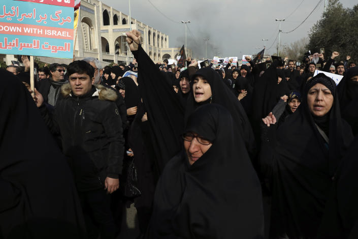 """A woman clenches her fist as she chants slogan while a man holds an anti-Israeli placard during a demonstration over the U.S. airstrike in Iraq that killed Iranian Revolutionary Guard Gen. Qassem Soleimani in Tehran, Iran, Jan. 3, 2020. Iran has vowed """"harsh retaliation"""" for the U.S. airstrike near Baghdad's airport that killed Tehran's top general and the architect of its interventions across the Middle East, as tensions soared in the wake of the targeted killing. (AP Photo/Vahid Salemi)"""