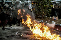Riot police officers react as a molotov cocktail explodes nearby during a clash with student protesters in Bandung, West Java, Indonesia, Monday, Sept. 30, 2019. Thousands of Indonesian students resumed protests in several cities on Monday against a new law they say has crippled the country's anti-corruption agency, with some clashing with police. (AP Photo/Kusumadireza)