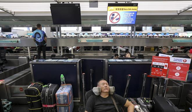 Travellers try to get some rest at Hong Kong International Airport early on Wednesday as flight operators play catch-up after air travel was plunged into disarray by protests. Photo: K.Y. Cheng