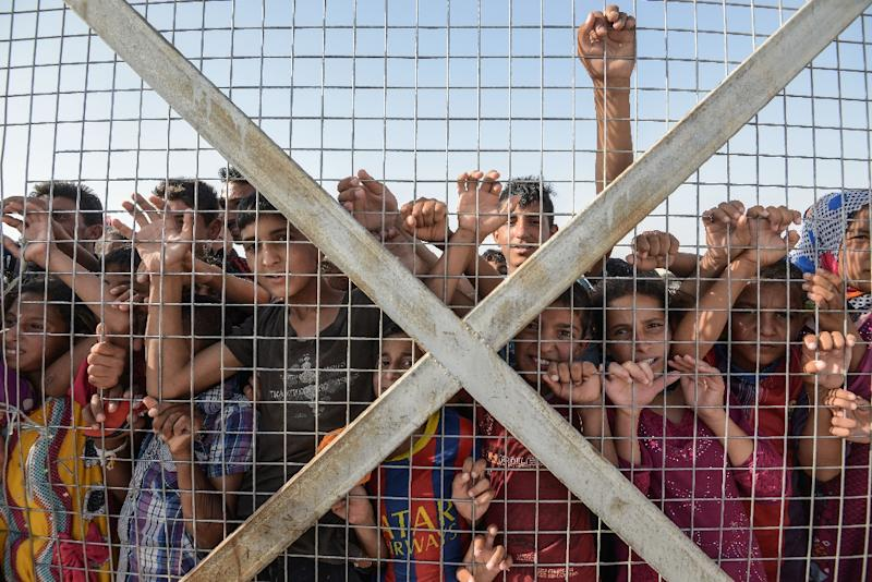 Displaced Iraqi children gather behind a fence at the Hasan Sham camp for internally displaced people east of Mosul, Iraq on June 10, 2017