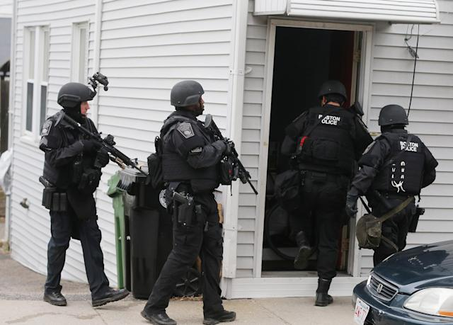 WATERTOWN, MA - APRIL 19: SWAT team members search for one remaining suspect at a residential building on April 19, 2013 in Watertown, Massachusetts. Earlier, a Massachusetts Institute of Technology campus police officer was shot and killed at the school's campus in Cambridge. A short time later, police reported exchanging gunfire with alleged carjackers in Watertown, a city near Cambridge. According to reports, one suspect has been killed during a car chase and the police are seeking another - believed to be the same person (known as Suspect Two) wanted in connection with the deadly bombing at the Boston Marathon earlier this week. Police have confirmed that the dead assailant is Suspect One from the recently released marathon bombing photographs. (Photo by Mario Tama/Getty Images)