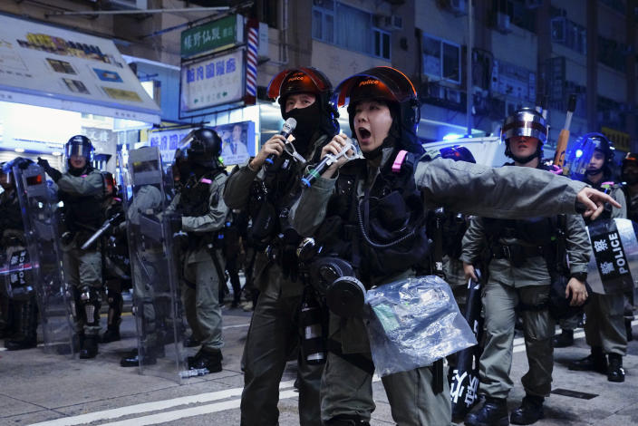 Police officers using speakers to warn protesters on the street of Yuen Long, Hong Kong, Monday, Oct. 21, 2019. A evening sit-in at a suburban train station on the three-month anniversary of a violent attack there on protesters by men with suspected organized crime ties. (AP Photo/Vincent Yu)