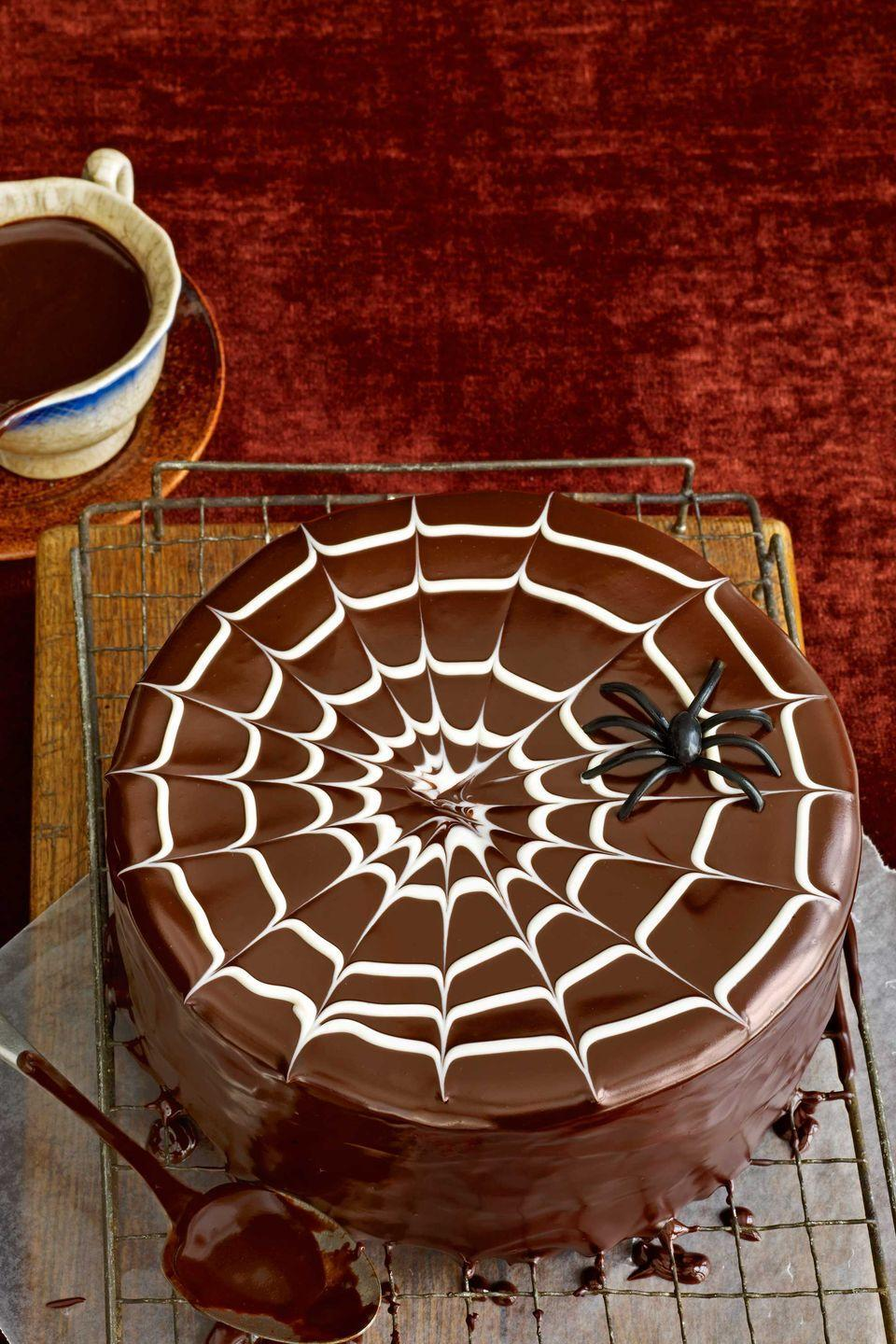 """<p>For a wickedly good web, pour Chocolate Glaze over the top of an uniced layer cake. Spread the glaze over the cake's edges and smooth the sides. Fill a small piping bag with three to four tablespoons of melted white chocolate, then starting at the center of the top of the cake, pipe the white chocolate in a spiral. Drag a toothpick from the center of the spiral to the cake's edge. Repeat every 1.5 inches to create a web effect.</p><p><strong><a href=""""https://www.countryliving.com/food-drinks/recipes/a2424/chocolate-glaze/"""" rel=""""nofollow noopener"""" target=""""_blank"""" data-ylk=""""slk:Get recipe for chocolate glaze"""" class=""""link rapid-noclick-resp"""">Get recipe for chocolate glaze</a>.</strong></p>"""
