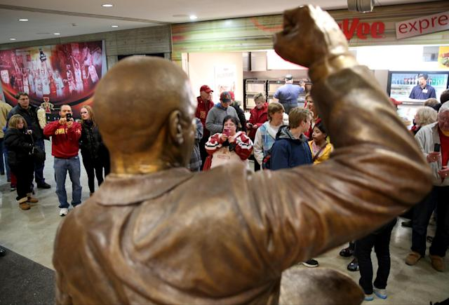 Fans stop by to look at and take pictures of the statue of former Iowa State coach Johnny Orr before Iowa State's NCAA college basketball game against Northern Illinois at Hilton Coliseum in Ames, Iowa., Tuesday, Dec. 31, 2013. Orr, 86, who also coached at Michigan, has died, Iowa State confirmed Tuesday. (AP Photo/Justin Hayworth)