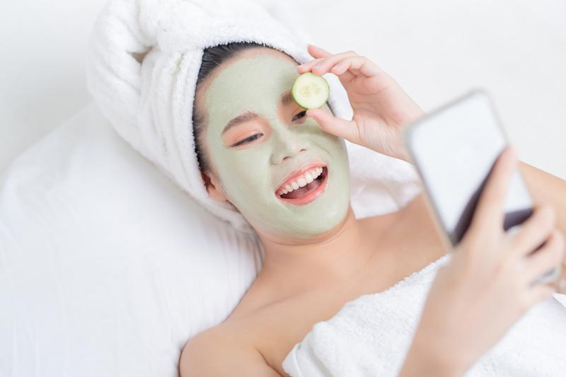 Asian woman is facial mask at home. She is live for her friends.