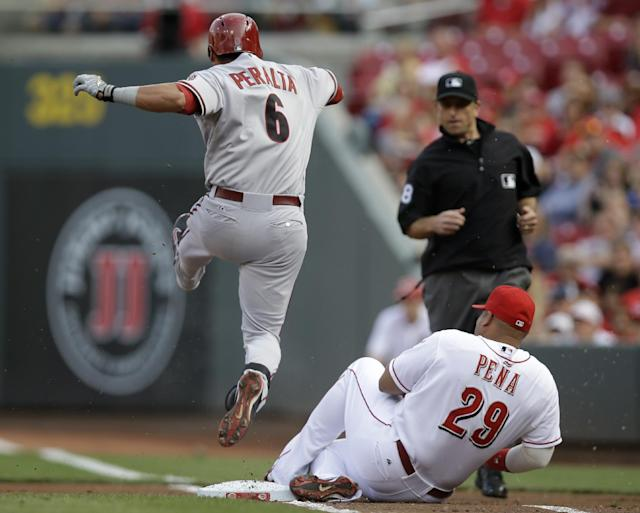 Arizona Diamondbacks' David Peralta (6) jumps over Cincinnati Reds first baseman Brayan Pena (29) after Pena fielded a ground ball and forced Peralta out at first base in the first inning of a baseball game, Monday, July 28, 2014, in Cincinnati. (AP Photo/Al Behrman)
