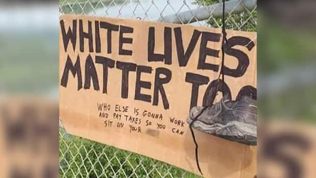 Muskoday First Nation Chief Ava Bear said multiple people reported seeing a man hang this sign and a pair of shoes on the fencing of the bridge over the South Saskatchewan River near the community. (Submitted by FSIN - image credit)