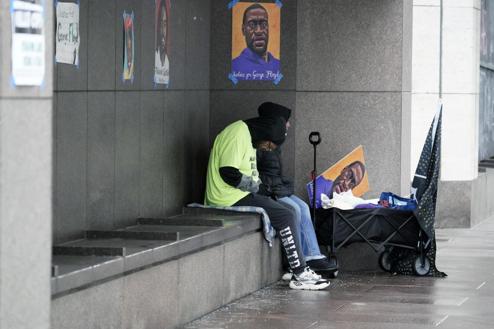 Two people with a George Floyd sign sit in a sheltered spot across the street from the Hennepin County Government Center, Wednesday, March 17, 2021, in Minneapolis where the trial for former Minneapolis police officer Derek Chauvin continues with jury selection. Chauvin is charged with murder in the death of George Floyd during an arrest last may in Minneapolis. AP Photo/Jim Mone)