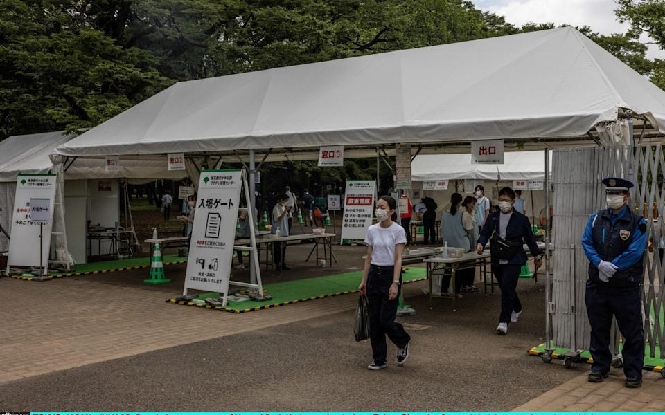 People leave an area of Yoyogi Park that was due to be a Tokyo Olympics fan park but has now been turned into a mass COVID-19 vaccination site - Carl Court/Getty Images AsiaPac