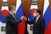 Russian Foreign Minister Sergey Lavrov, left, bumps elbows with South Korean Foreign Minister Chung Eui-yong after a joint announcement at the Foreign Ministry in Seoul, South Korea, Thursday, March 25, 2021. (AP Photo/Ahn Young-joon, Pool)